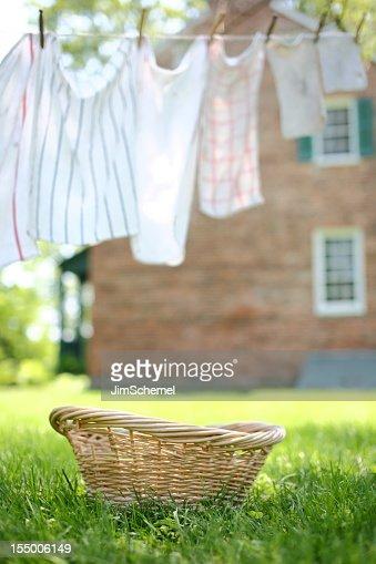 An empty wicker basket beneath an outdoor clothesline