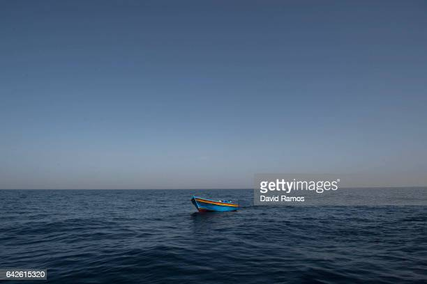 An empty wooden boat is left behind after migrants and refugees were assisted by members of the Spanish NGO Proactiva Open Arms as they crowd it...