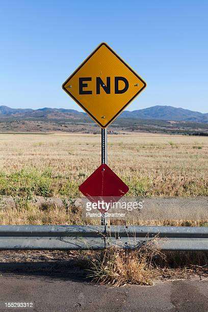 An END road sign and mountain ranges behind