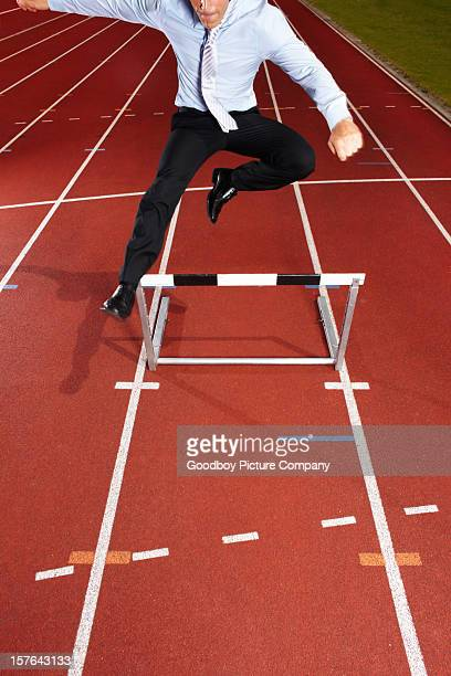 An energetic businessman is jumping over the hurdle