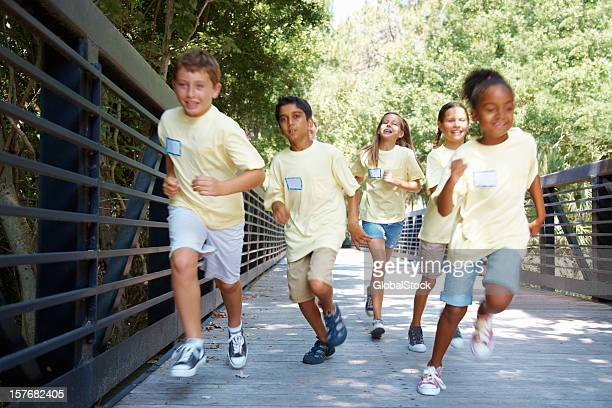 An energetic field trip students running on a wooden bridge