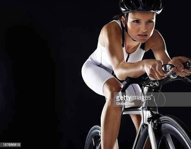 An energetic woman riding bicycle against black background