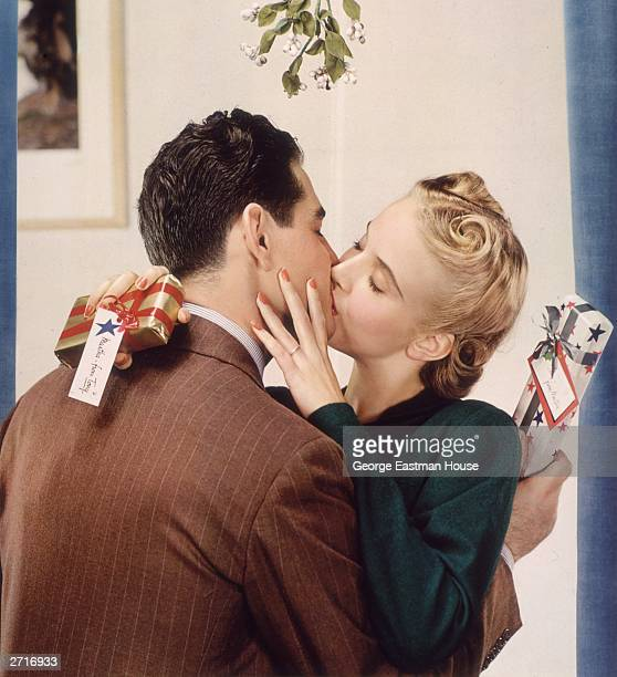 An engaged couple both holding Christmas presents kiss under mistletoe