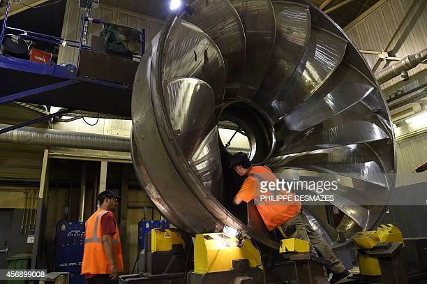 An engineer checks a pumpturbine at the Alstoms global technology and hydropower centre in Grenoble eastern France on October 8 2014 The centre which...