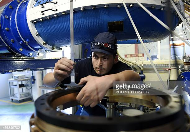 An engineer checks an element of a pumpturbine at the Alstoms global technology and hydropower centre in Grenoble eastern France on October 8 2014...