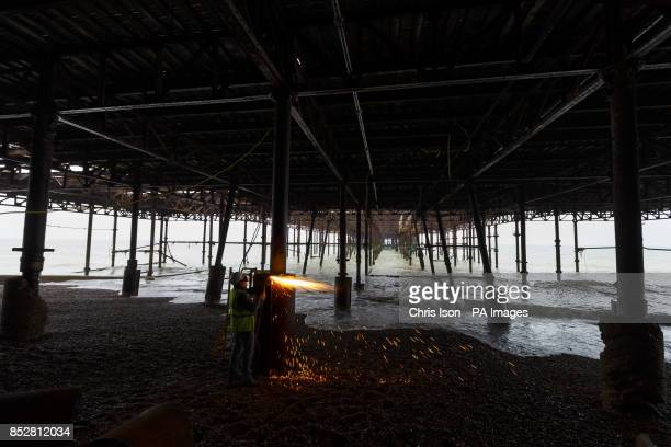 An engineer cuts steel footings under Hastings Pier as the 16 month 13 million restoration project begins following the devastating fire in 2010
