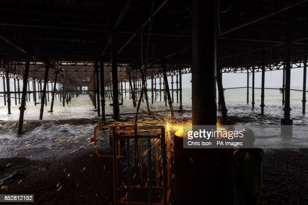 An engineer cuts steel footings under Hastings Pier as the 16 month Acircpound13 million restoration project begins following the devastating fire in...