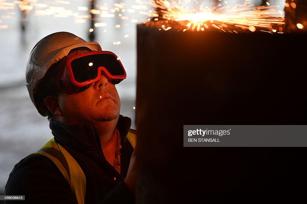 An engineer cuts steel in order to replace a missing beam under the burnt-out remains of Hastings Pier in Hastings, southern England, on December 13, 2013 ahead of the start of a multi-million pound regeneration project. Hastings Pier was originally constructed in opulent style in the late 19th century seeing its heyday in the 1930s and hosting music concerts by major artists including The Rolling Stones in the 1960s and 70s. After undergoing various additions and re-construction to repair storm and fire damage throughout the 20th century the Victorian pier finally suffered a devastating fire in 2010 which destroyed much of the superstructure leaving just a burnt out shell. Following a Heritage Lottery Fund (HLF) grant and money from other funds a 14 million GBP regeneration project is set to begin work on January 6, 2014.