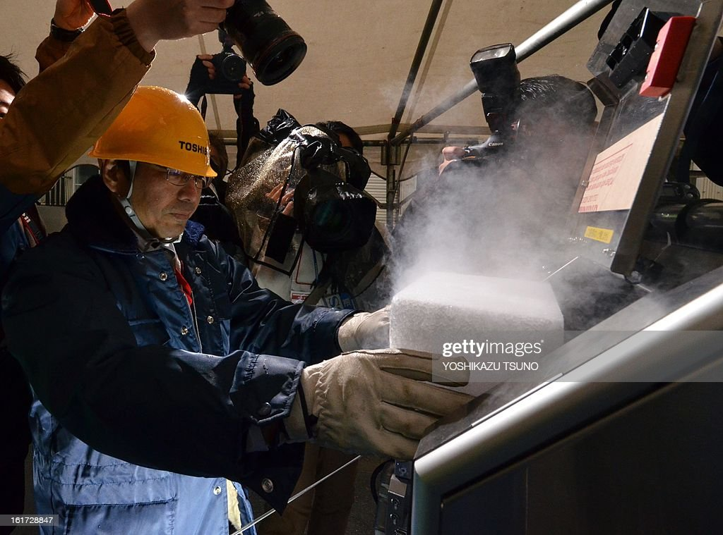 An engineer from Toshiba puts a block of dry ice into a decontamination robot, for work inside a nuclear plant, during a demonstration at Toshiba's technical center in Yokohama, suburban Tokyo on February 15, 2013. The crawler robot blasts dry ice particles against contaminated floors or walls and will be used for the decontamination in TEPCO's stricken Fukushima nuclear power plant. AFP PHOTO / Yoshikazu TSUNO