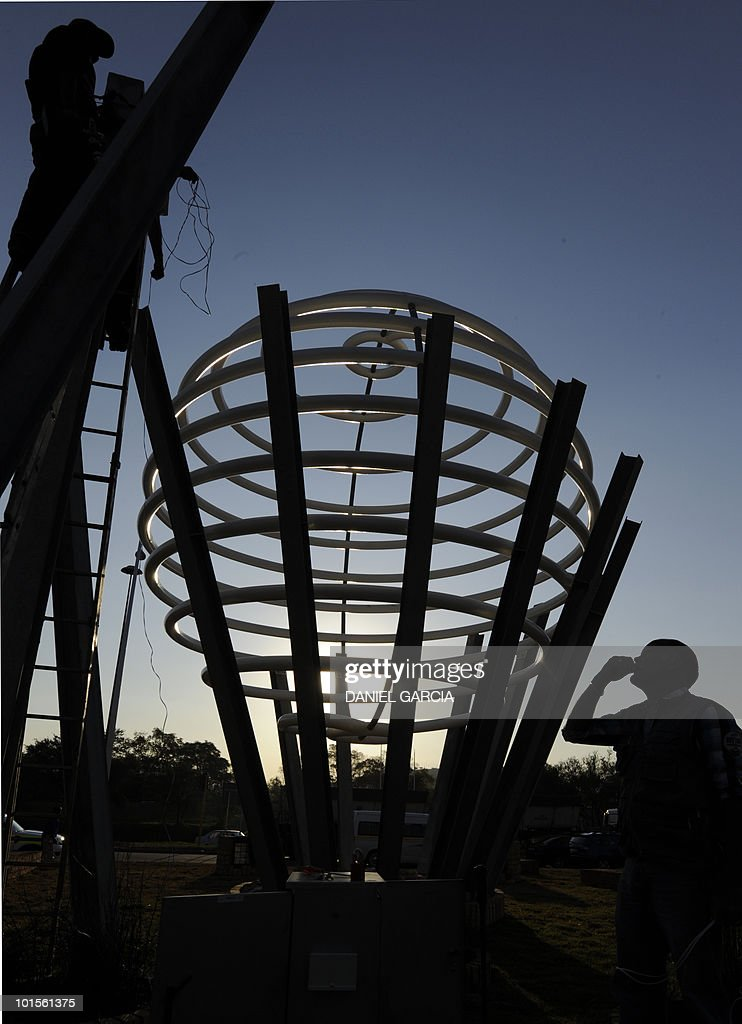 An engineer gives instructions to a worker to conect wires to light a giant football made with electrical tubes at a roundabout on June 2, 2010 in Pretoria. The FIFA football World Cup will begin on June 11,2010 with the match between South Africa and Mexico.