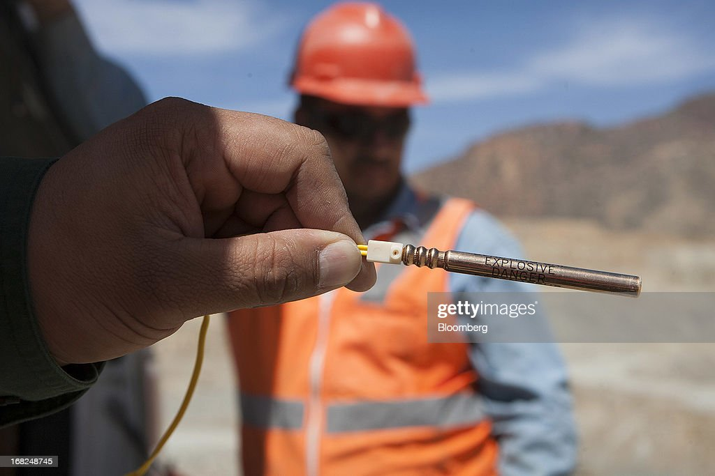 An engineer holds an electrical wiring system for a photograph to be used to activate a controlled explosion at Grupo Mexico SAB's La Caridad open pit copper mine in Sonora, Mexico, on Monday, May 6, 2013. Grupo Mexico SAB, Mexico's biggest mining company by market value, estimates it will produce 840,000 tons of copper in 2013. Photographer: Susana Gonzalez/Bloomberg via Getty Images
