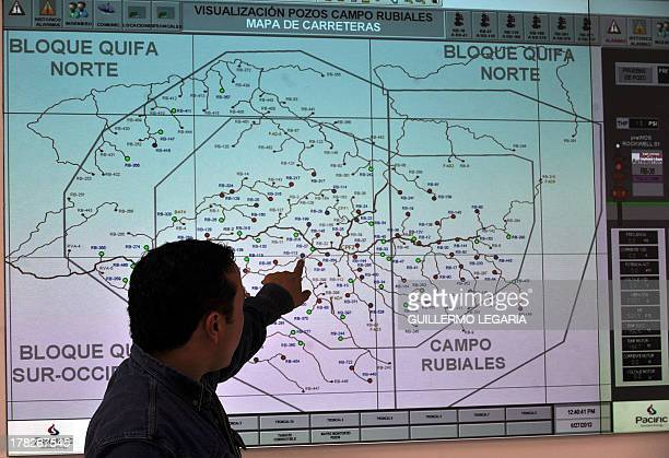 An engineer of Canadian oil company Pacific Rubiales shows a map with the location of the oil wells at Colombia's main oilfield Rubiales in Meta...