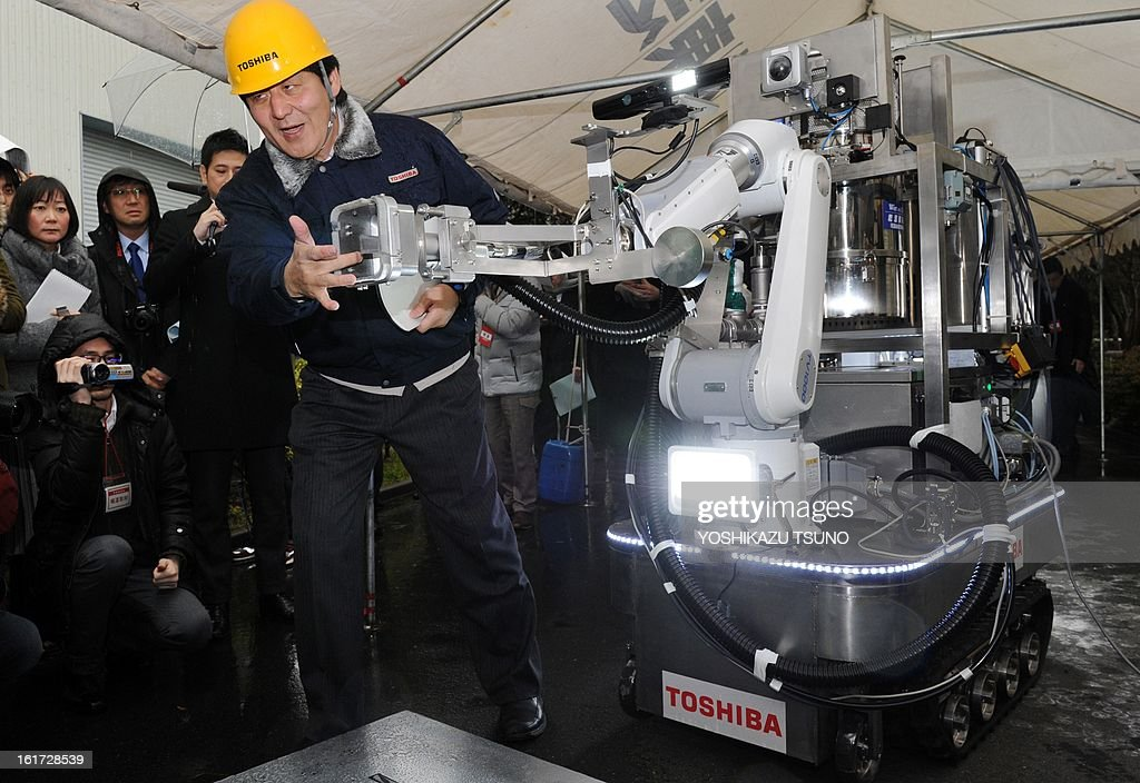 An engineer of Toshiba displays a decontamination robot, for work inside a nuclear plant, during a demonstration at Toshiba's technical center in Yokohama, suburban Tokyo on February 15, 2013. The crawler robot blasts dry ice particles against contaminated floors or walls and will be used for the decontamination in TEPCO's stricken Fukushima nuclear power plant. AFP PHOTO / Yoshikazu TSUNO