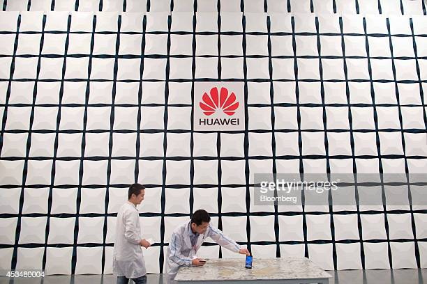 An engineer sets up a smartphone for testing inside a semianechoic chamber in the global compliance and testing center at the Huawei Technologies Co...