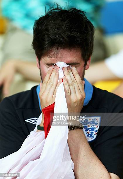 An England fan cries into a St George's Cross flag during the UEFA EURO 2012 quarter final match between England and Italy at The Olympic Stadium on...