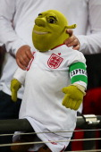 An England fan holds a toy Shrek dressed in a Wayne Rooney replica England shirt with a captain's armband during the FIFA 2014 World Cup Group H...
