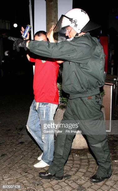 An England fan is escorted away from the Alter Markt as trouble flares in Cologne Germany before England's third World Cup match againt Sweden