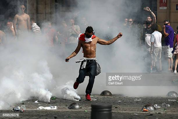 An England fan kicks a tear gas canister as fans clash with police ahead of the game against Russia later today on June 11 2016 in Marseille France...