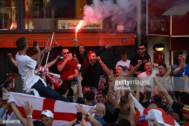 An England football fan holds a flare as they gather outside a pub on June 15 2016 in Lille France Police used tear gas and pepper spray on the fans...