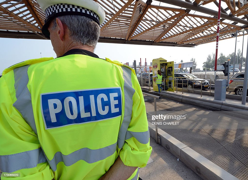 An English police officer checks vehicles at a toll station in Fresnes-les-Montauban, near Arras northern France, on July 6, 2013, working in collaboration with Belgian, Dutch and French police officers during the first wave of departures for the summer holiday.