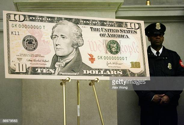 An enlarged print of the redesigned $10 bill is displayed next to a security officer during a news conference to commemorate the first day of...