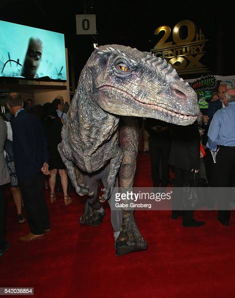 An entertainer dressed as a velociraptor walks with attendees during the Licensing Expo 2016 at the Mandalay Bay Convention Center on June 21 2016 in...