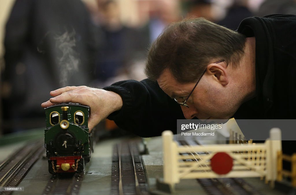 An enthusiast adjusts a locomotive at The London Model Engineering Exhibition at Alexandra Palace on January 18, 2013 in London, England. The exhibition features more than a thousand models from over 50 national and regional clubs and societies. A wide range of locomotives, boats and aircraft are on show.