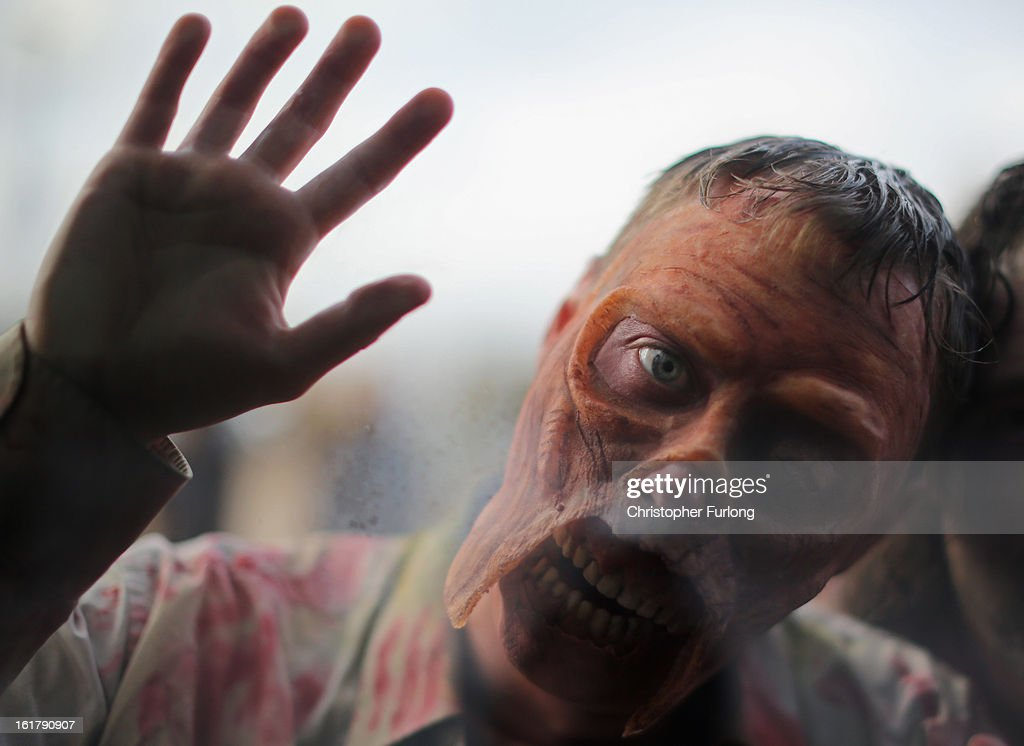 An enthusiast dressed up as a Zombie pushes himself towards a window during the MCM Midlands Comic Con Expo at The International Centre on February 16, 2013 in Telford, England. Enthusiasts at the Comic Convention are encouraged to wear a costume of their favourite comic character and flock to the Expo to gather all the latest news in the world of comics, manga, anime, film, cosplay, games and cult fiction.