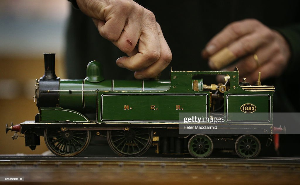 An enthusiast makes adjustments to a locomotive at The London Model Engineering Exhibition at Alexandra Palace on January 18, 2013 in London, England. The exhibition features more than a thousand models from over 50 national and regional clubs and societies. A wide range of locomotives, boats and aircraft are on show.