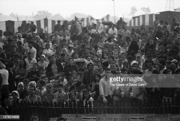 An enthusiastic folk music audience playfully endure a rain storm during the Newport Folk Festival in July 1965 in Newport Rhode Island