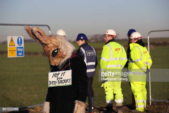 An environmental activist dressed as a rabbit poses with a sign saying 'hop it you dirty frackers' as workmen begin the construction of the shale gas...