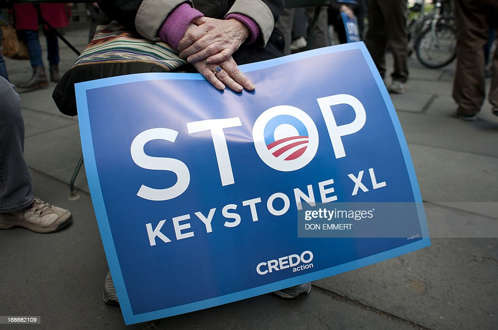 An environmental activist holds a sign in Bryant Park, protesting the proposed Keystone XL pipeline, May 13, 2013 in New York. The group marched through midtown to rally outside the Waldorf Astoria hotel where President Obama was attending a fundraiser. AFP PHOTO/Don Emmert