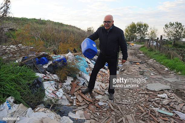 An environmental activist shows plastic and asbestos strewn on the sides of an agriculture field near Orta di Atella southern Italy on November 14...