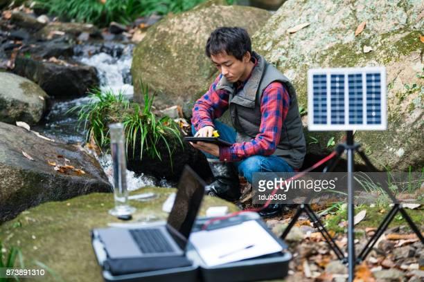 Milieu ingenieur werkzaam bij een zonne-aangedreven Proefstation voor de controle van de waterkwaliteit