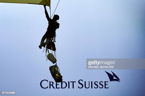 An environmental group Greenpeace activist hanging on ropes mounts a banner reading 'Credit Suisse Stop dirty pipeline deals' as Credit Suisse CEO...