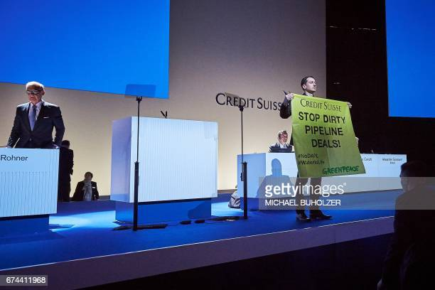 An environmental group Greenpeace activist holds a banner reading 'Credit Suisse Stop dirty pipeline deals' as chairman Urs Rohner attends the annual...