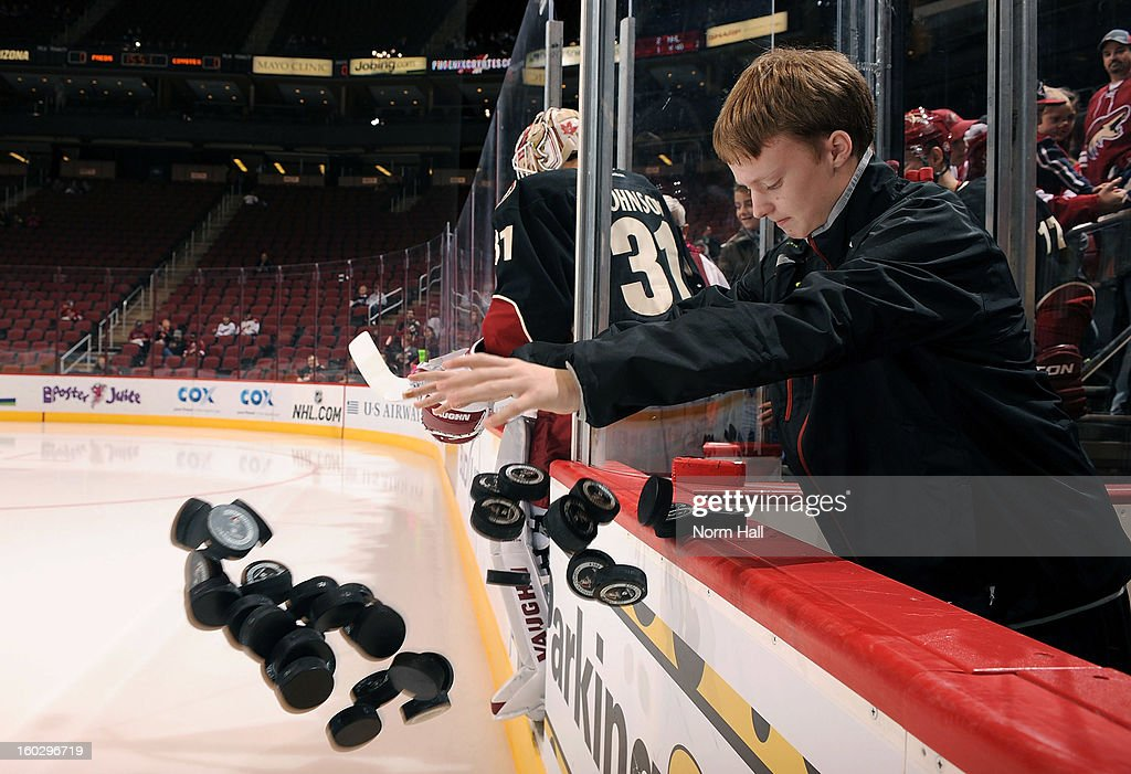 An equipment manager with the Phoenix Coyotes dumps practice pucks on the ice before the start of a game against the Nashville Predators at Jobing.com Arena on January 28, 2013 in Glendale, Arizona.