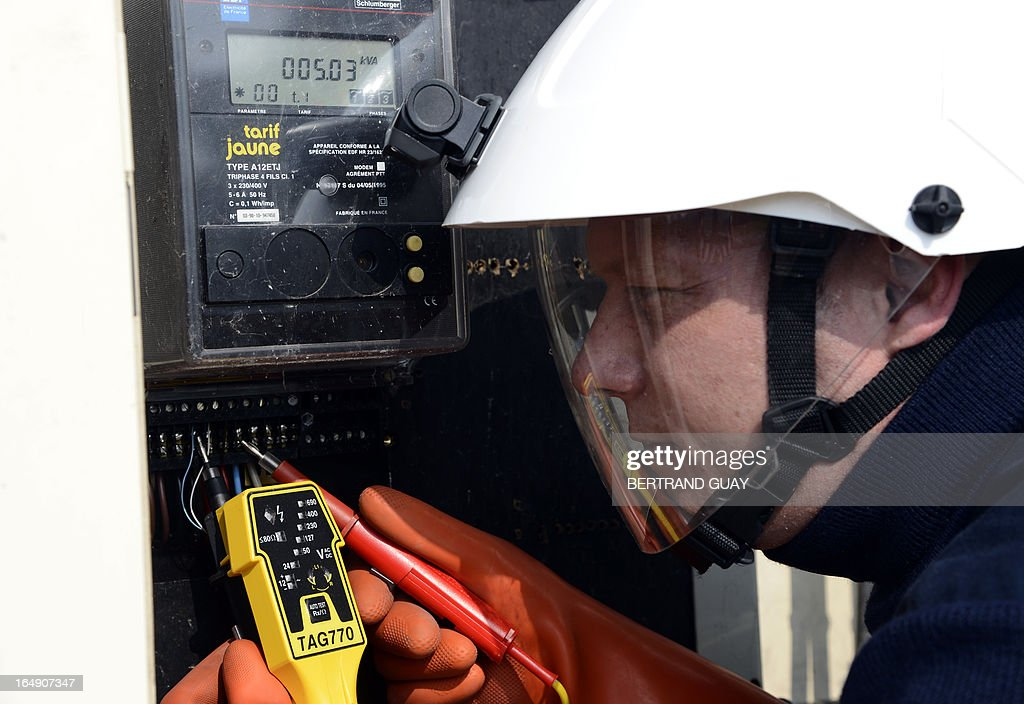 An ERDF (Electricity Network Distribution France) technician, controls an electricity meter at the site of ERDF in Saint-Ouen-l'Aumone, near Paris, on March 29, 2013.
