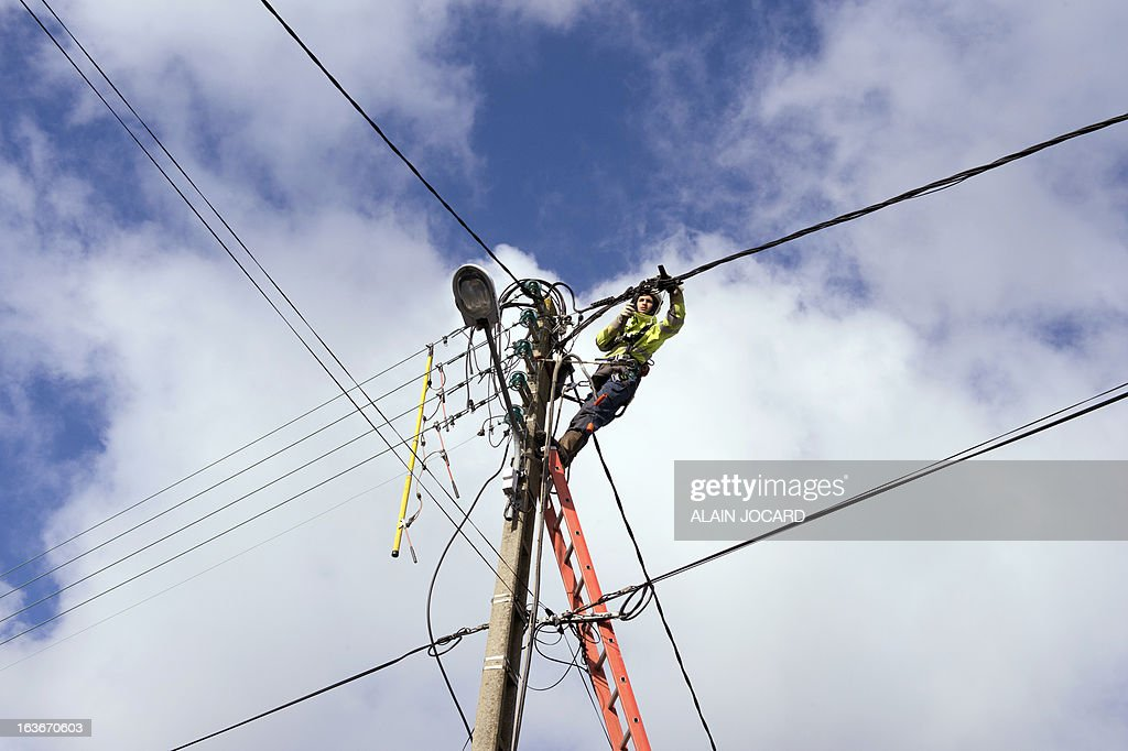 An ERDF (Electricity Network Distribution France) technician fixes a damaged power line after heavy snowfalls on March 14, 2013 in Gatteville-Le-Phare, , northern France. More than 68,000 homes were without electricity in France and hundreds of people were trapped in their cars after a winter storm hit with heavy snow, officials and weather services said on March 12. Twenty-six regions in northwest and northern France were put on orange alert because of heavy snowfalls, which Meteo France said were 'remarkable for the season because of the expected quantity and length of time'. AFP PHOTO / ALAIN JOCARD