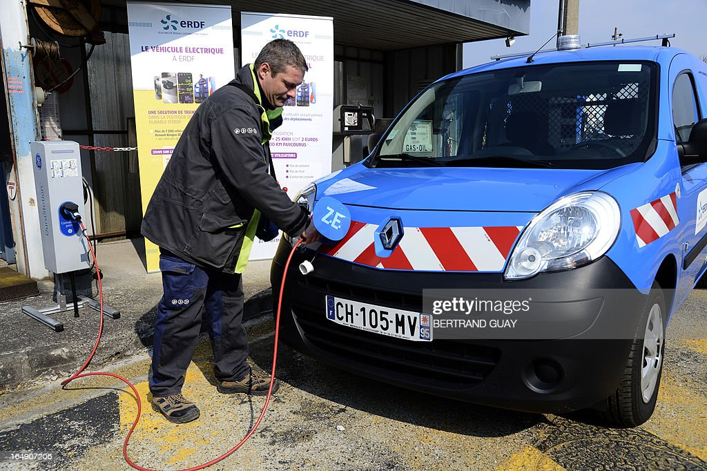 An ERDF (Electricity Network Distribution France) technician, recharges an electric car at the site of ERDF in Saint-Ouen-l'Aumone, near Paris, on March 29, 2013. AFP PHOTO BERTRAND GUAY