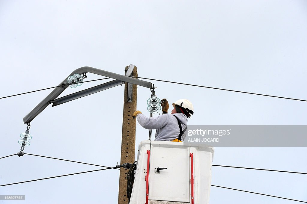 An ERDF (Electricity Network Distribution France) technician repairs a damaged power line after heavy snowfall on March 13, 2013 in Digulleville, northern France. More than 68,000 homes were without electricity in France and hundreds of people were trapped in their cars after a winter storm hit with heavy snow, officials and weather services said on March 12. Twenty-six regions in northwest and northern France were put on orange alert because of heavy snowfalls, which Meteo France said were 'remarkable for the season because of the expected quantity and length of time'. AFP PHOTO / ALAIN JOCARD