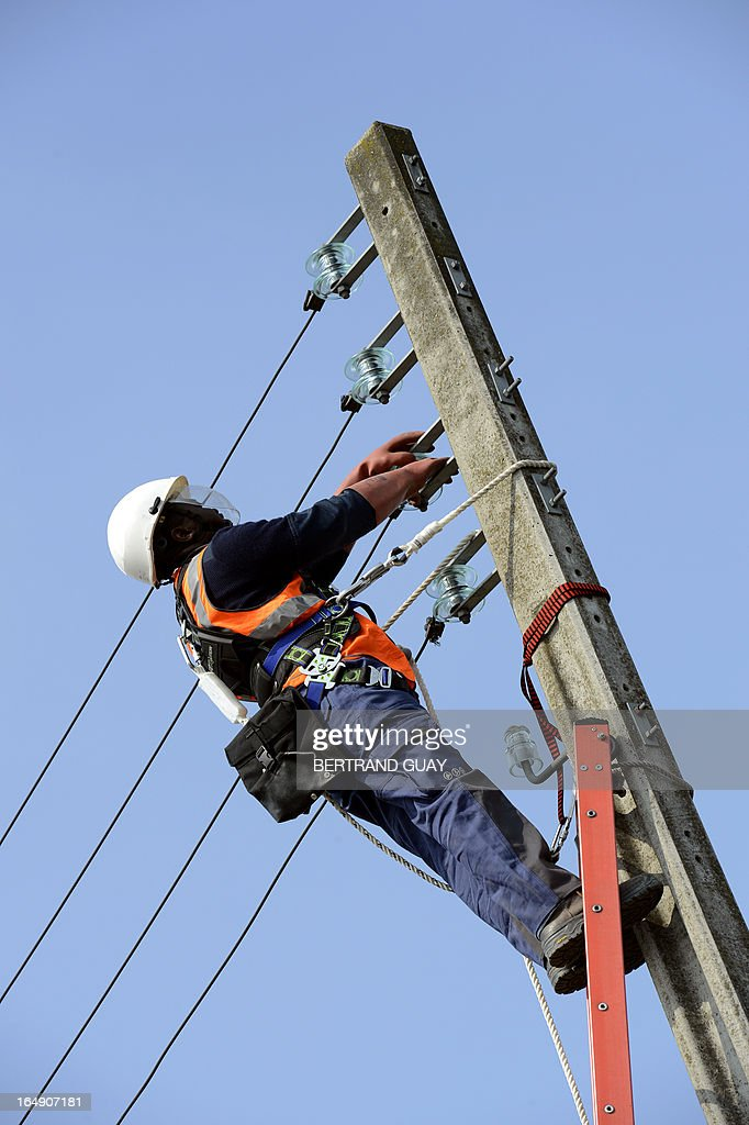 An ERDF (Electricity Network Distribution France) technician works on a power line, at the site of ERDF in Saint-Ouen-l'Aumone, near Paris, on March 29, 2013. AFP PHOTO BERTRAND GUAY