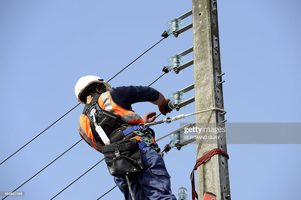 An ERDF (Electricity Network Distribution France) technician works on a power line, at the site of ERDF in Saint-Ouen-l'Aumone, near Paris, on March 29, 2013.