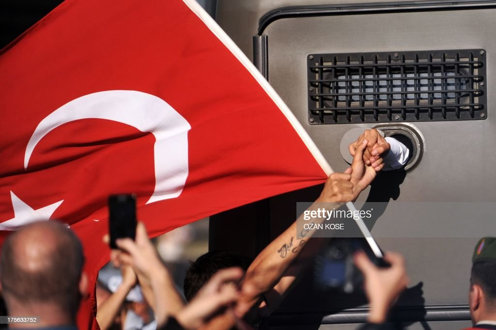 An Ergenekon prisoner being driven in a police armoured vehicle holds a protestor's hand on August 5 as police and gendarmerie block access to a...