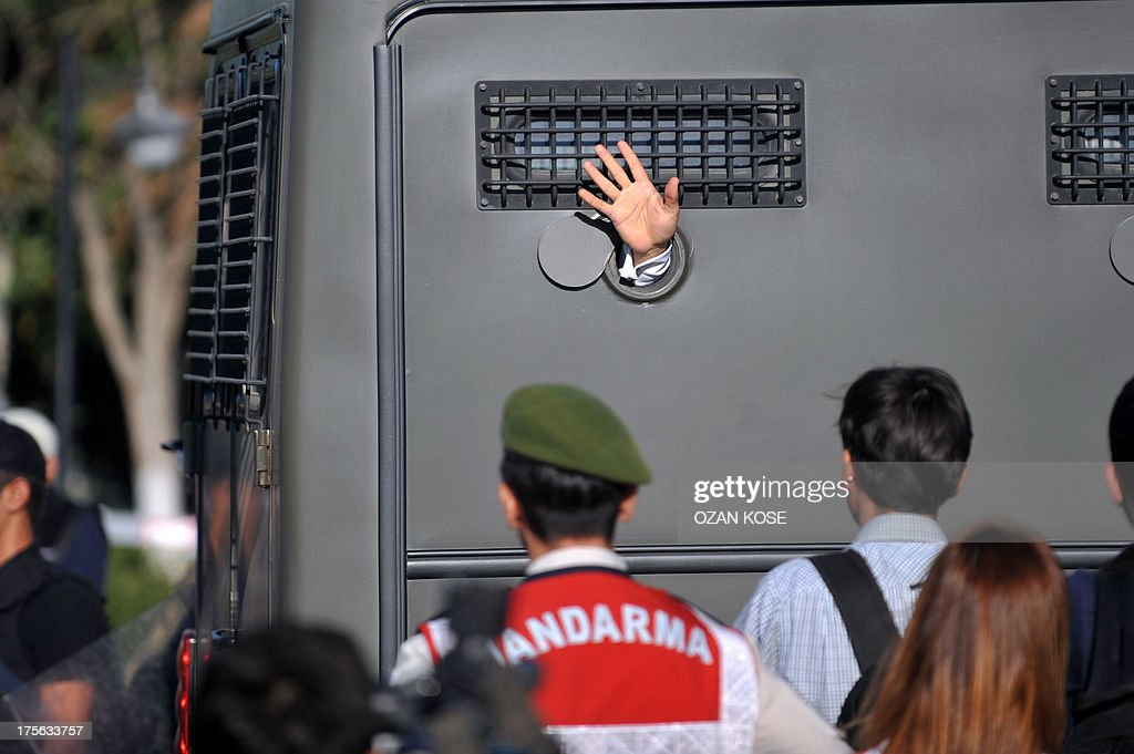 An Ergenekon prisoner being driven in a police armoured vehicle waves at protestors on August 5, 2013, as police and gendarmerie block access to a courthouse in Silivri, near Istanbul, where prosecutors are scheduled to deliver their final arguments in the case against 275 people accused of plotting to overturn the Islamic-leaning government. Among the defendants in the high-profile case -- seen as a key test in Prime Minister Recep Tayyip Erdogan's showdown with secularist and military opponents -- are ex-military chief Ilker Basbug and other army officers as well as lawyers, academics and journalists. AFP PHOTO/OZAN KOSE