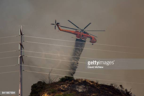 An Erickson Air Crane firefighting helicopter drops fire retardant next to high power lines that could become overheated by flames at the La Tuna...