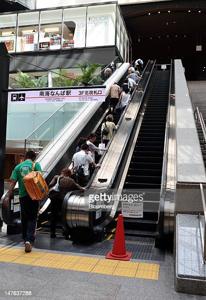 An escalator is stopped right to save electricity while people ride escalators at a station in Osaka Japan on Monday July 2 2012 Even with the start...