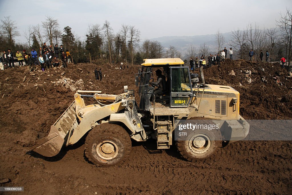 An escavator is used after the rescue mission is finished in the disaster-hit area in Gaopo village, southwest China's Yunnan province on January 12, 2013. Three people remain missing after a landslide which killed 43, including seven from a single family, struck a remote village in southwestern China, state media said on January 12. CHINA OUT AFP PHOTO