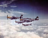 An escort of North American P51 Mustangs from the 361st Fighter Group 8th Air Force in flight during a mission July 1944 Note the auxiliary tanks...