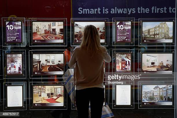 An estate agent arranges a photographic display of exteriors and interiors of available residential properties in London UK on Monday Dec 30 2013 UK...